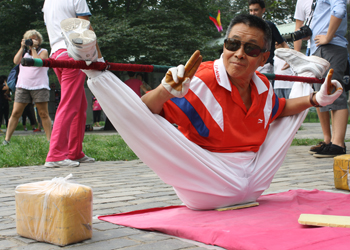 An elderly man demonstrates his stretching ability
